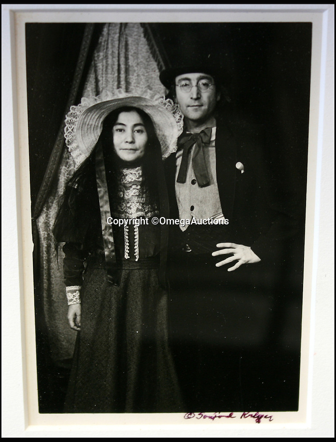 BNPS.co.uk (01202 558833)<br /> Pic: OmegaAuctions/BNPS<br /> <br /> John Lennon with his wife Yoko Ono.<br /> <br /> A remarkable set of family photos that show John Lennon larking around and dressing as a woman have emerged for sale.<br /> <br /> The five original black and white pictures offer a rare insight into the personal life of the mega star and show Lennon, his wife Yoko Ono and baby son Sean having fun in costume while on holiday in America. <br /> <br /> They were taken in a vintage clothing photography studio in Stockbridge, Massachusetts in 1977 - just three years before the music icon was shot outside his New York apartment - and also feature Sean's nanny and a friend.