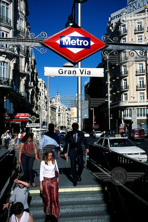 People walk down into Grand Via Metro station. Grand Via is the Madrid's main shopping street...