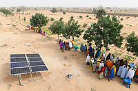 NIGER, Maradi, village Dan Bako, project poverty reduction and adaption of climate change, vegetable farming with irrigation , water is pumped by solar powered pump, women at solar panel / Projekt Armutsbekaempfung und Anpassung an den Klimawandel, Gemuesegarten mit Bewässerung, Solar Panel für Wasserpumpe zur Bewässerung