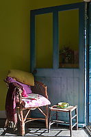 A wicker chair and stool have been positioned by the open front door to take advantage of a patch of sunlight