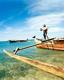 MADAGASCAR, boy holding fish standing on dugout canoe, Nosy Komba