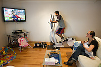 A young mother breastfeeds her baby while watching television in her living room and her husband woks out on his excercise machine.<br /> <br /> 15/05/2012<br /> Hampshire, England, UK