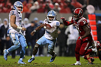 RALEIGH, NC - NOVEMBER 30: Michael Carter #8 of the University of North Carolina is chased by Jarius Morehead #31 of North Carolina State University during a game between North Carolina and North Carolina State at Carter-Finley Stadium on November 30, 2019 in Raleigh, North Carolina.