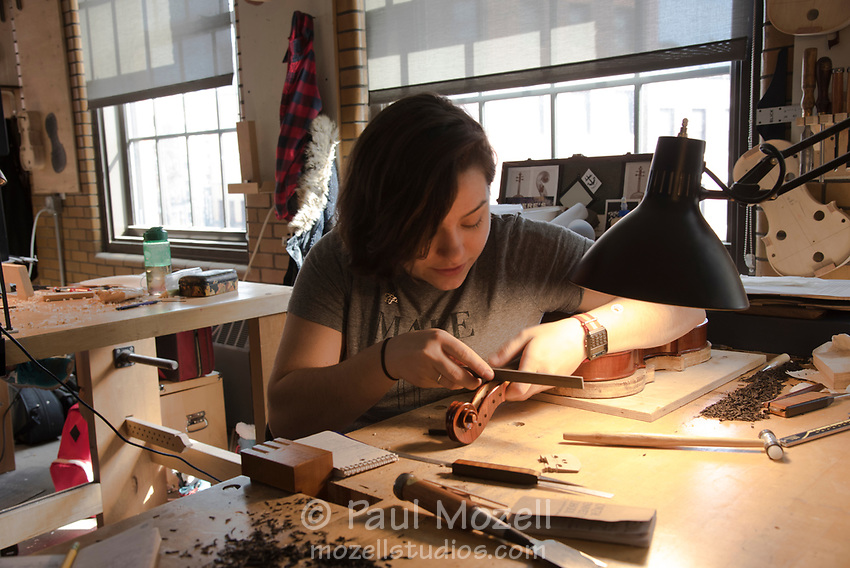 Student Brooke Esplin studies the instrument she is making in the Violin Making and Repairing program at The North Bennett Street School