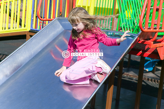 Little girl playing on a slide in the playground,