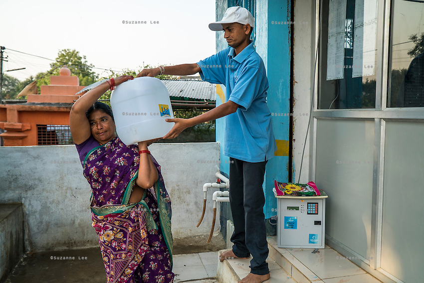 The iJal station operator helps a woman carry her full can of safe water from the iJal station in Peddapur, a remote village in Warangal, Telangana, India, on 22nd March 2015. Safe Water Network works with local communities that live beyond the water pipeline to establish sustainable and reliable water treatment stations within their villages to provide potable and safe water to the communities at a nominal cost. Photo by Suzanne Lee/Panos Pictures for Safe Water Network
