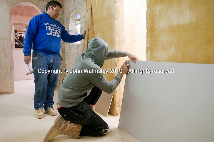 Plastering student cutting some plasterboard to length, Able Skills, Dartford, Kent.