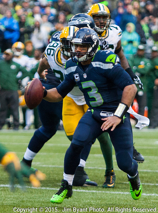 Seattle Seahawks  quarterback  Russell Wilson (3) runs to a one-yard touchdown against the Green Bay Packers during the NFC Championship game at CenturyLink Field in Seattle, Washington on January 18, 2015.  The Seattle Seahawks beat the Green Bay Packers in overtime 28-22 for the NFC Championship Seattle.  ©2015. Photo by Jim Bryant.  All Rights Reserved.
