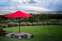 Umbrella and table in Alii Kula Lavender Farm, with rainbow. Maui, Hawaii