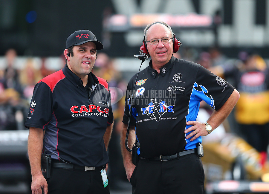 Jun 19, 2015; Bristol, TN, USA; Crew member Bobby Lagana for NHRA top fuel driver Steve Torrence (left) with Mike Guger , crew chief for top fuel driver Larry Dixon during qualifying for the Thunder Valley Nationals at Bristol Dragway. Mandatory Credit: Mark J. Rebilas-