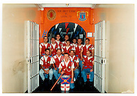 A photographs of Tommy and his friends inside the Maze prison. They are all wearing identical waistcoats with loyalist badges and paraphernalia. A mural on the wall above them reads: 'Our only crime is loyalty.' Tommy's comment on the image: 'The band inside the Maze in 1993. Some of these lads have since died God bless them.' (The Maze prison, on the site of a former Royal Airforce station of Long Kesh on the outskirts of Lisburn in Northern Ireland, was used during the Troubles, a period of intercommunal violence and strife which lasted for approximately 3 decades from the 1960s to 1998, when the Good Friday Agreement ended outright hostilities, to house paramilitary prisoners. It was closed in 2000 and partly demolished.).