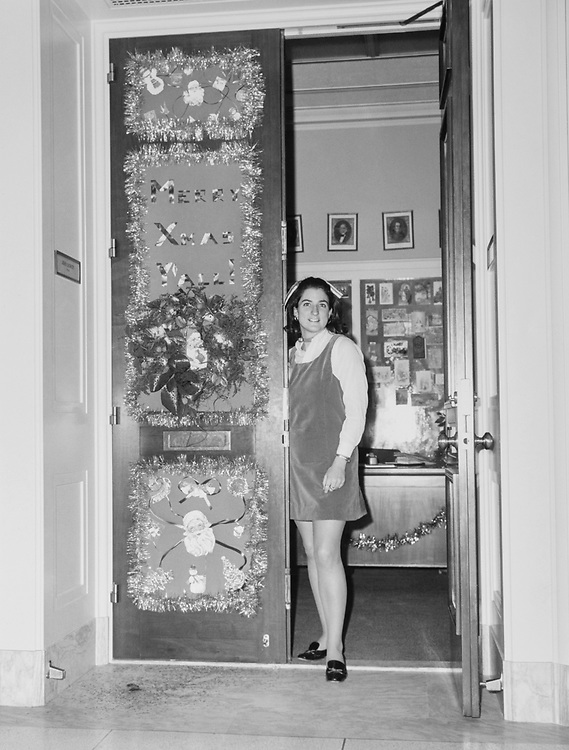 Staff member standing at the doorway of decorated Congressman's office around Christmas. (Photo by CQ Roll Call via Getty Images)