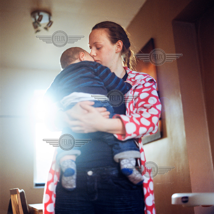 Maxine hold her son Cohen at their home in Tigers Bay, a loyalist area in Belfast. Maxine and her boyfriend Mucker were forced to leave Northern Ireland after he was accused of selling drugs by the Ulster Volunteer Force (UVF) paramilitary group. After two years in Scotland they returned and Mucker joined the Ulster Defence Association (UDA) in an attempt to seek protection.
