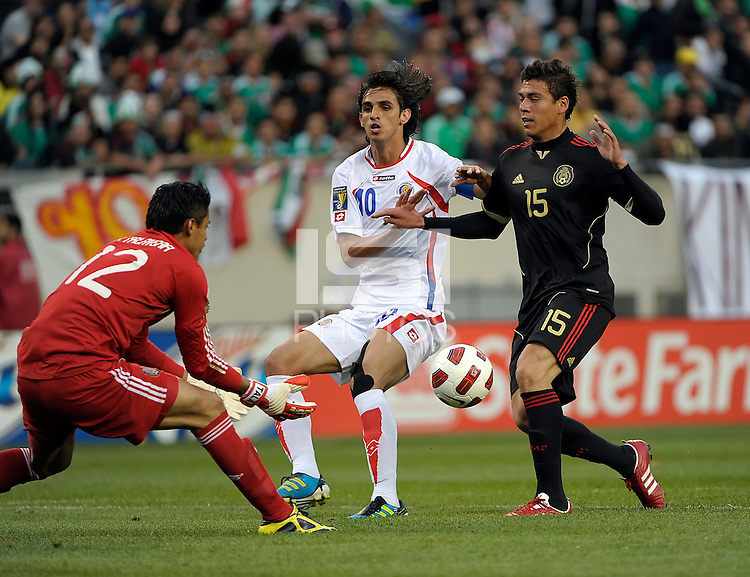 Mexico goalkeeper Alfredo Talavera comes out to make the save as Mexico's Hector Moreno shields Costa Rica's Bryan Ruiz from the ball.  Mexico defeated Costa Rica 4-1 at the 2011 CONCACAF Gold Cup at Soldier Field in Chicago, IL on June 12, 2011.