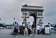 Paris, August 1977. Place de l'Étoile. August in Paris is a noveable feast. While millions of residents are leaving for their favourite resorts, thousands of foreign tourists are flocking to the French Capital. Nevertheless, genuine Parisians, old and young alike, stay in Paris and mantain the tradition charm.