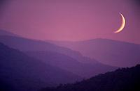 A crescent moon rises over a mountain range. Bennington, Vermont.