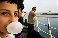ISTANBUL - MAY 26, 2007:   A boy blows a bubble while crossing the Bosphorus on the ferry in Istanbul, Turkey. Photo by Landon Nordeman.