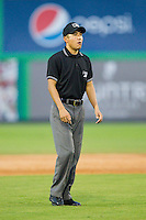 Umpire Takahito Matsuda handles the calls on the bases during the Appalachian League game between the Pulaski Mariners and the Burlington Royals at Burlington Athletic Park on July 20, 2013 in Burlington, North Carolina.  The Royals defeated the Mariners 6-5.  (Brian Westerholt/Four Seam Images)