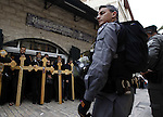 Israeli policemen stand guard in front of Orthodox Christians as they stand on the Via Dolorosa on their way to the Church of the Holy Sepulchre during the Good Friday processions retracing the route taken by Jesus Christ to his crucifixion, in Jerusalem's Old City on 10 April 2015. Photo by Saeb Awad