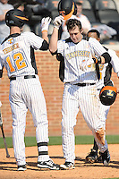 Matt Duffy #13 of the Tennessee Volunteers is greeted at home after hitting a Grand Slam at Lindsey Nelson Stadium against the the Manhattan Jaspers on March 12, 2011 in Knoxville, Tennessee.  Tennessee won the first game of the double header 11-5.  Photo by Tony Farlow / Four Seam Images..