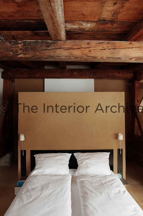 The headboard in this attic bedroom also serves as a partition behind which the bathroom can be found