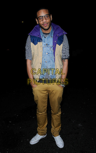 "REGGIE YATES.At ""The Good Rats"" Private View, Art Work Space, Hempel Hotel, London, England, UK, February 9th 2010..full length yellow mustard trousers striped shirt top blue purple sleeveless body warmer glasses white trainers denim waistcoat hands in pockets converse .CAP/CAN.©Can Nguyen/Capital Pictures."