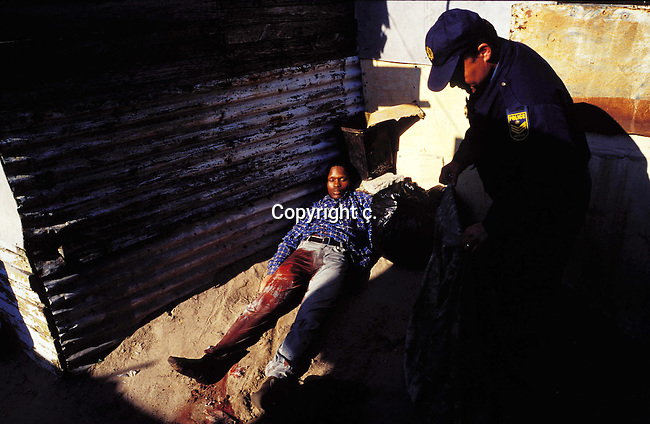DIPOLIC00102.Police.An unidentified policeman putting a blanket over a dead man outside a shack on August 15, 2001 in Site B Khayelitsha, a township about 35 kilometers outside Cape Town, South Africa. The man and two others came to rob people in the house and a firefight broke out. Khayelitsha is one of the poorest and fastest growing townships in South Africa. People usually come from the rural areas in Eastern Cape province to find work as maids and laborers. Most people don't find work and the unemployment rate is very high, together with lot of violence and a growing HIV-Aids epidemic itÕs a harsh area to live in..©Per-Anders Pettersson/iAfrika Photos.