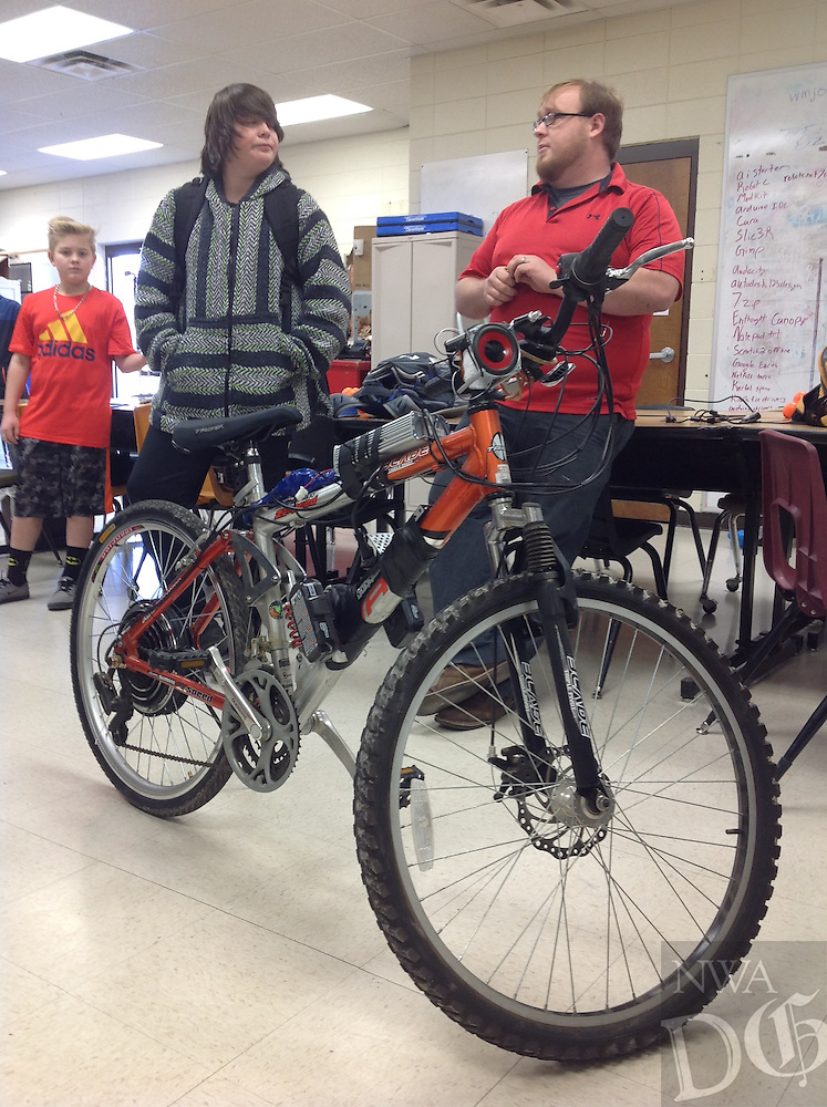 NWA Democrat-Gazette/Dave Perozek<br /> Blake Matthews (right), a science and technology teacher at Washington Junior High School, and eighth-grader Spencer Stevens, 14, stand behind an electric bicycle Spencer and other students assembled last month.
