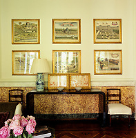 A series of 17th century drawing of houses and gardens hangs above a Chinese lacquered console table in the living room
