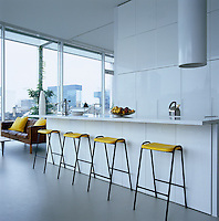 A row of Robin Day bar stools stand in front of the kitchen counter in this sleek white open-plan kitchen
