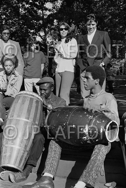October 1969, Manhattan, New York City, New York State, USA. French singer Sacha Distel with his wife Francine Breaud listening to drummers in Central Park, New York.