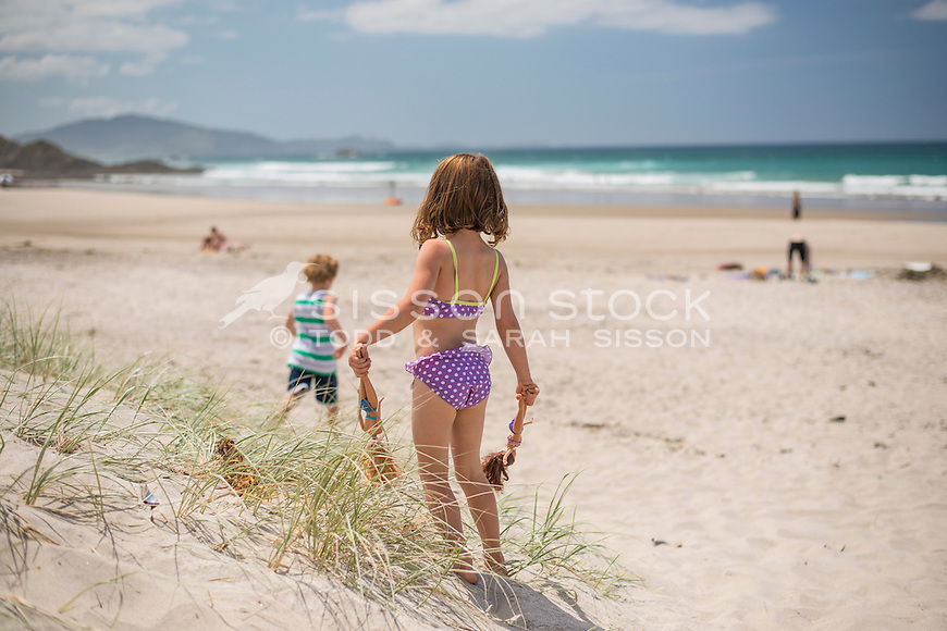 Little girl in a puple polka dot bikini holding dolls at the beach on a summer's day, Whangarei Heads, Northland New Zealand - stock photo, canvas, fine art print