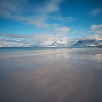 Mountain rise in distance across sea from beach at Gimsøy, Lofoten Islands, Norway