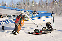 February 16, 2013  Volunteers help turn Greg Fischer's Cessna around at the Willow airport as musher food, straw, HEET and people food is flown to the 4 checkpoints on the east side the Alaska Range. ..Photo Copyright Jeff Schultz  -- Do not reproduce without written permission