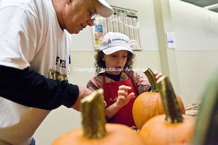 MIDDLEBURY, CT - 27 SEPTEMBER 2009 -092709JT04-<br /> Lou Orsini helps his granddaughter Morgan Murray, 8, decorate her second pumpkin at the Shepardson Community Center during the Saint John of the Cross Church Apple Harvest Festival on Sunday in Middlebury. Murray had decorated another pumpkin for her sister Sydney, who was at home sick. The event featured food, children's games, a silent auction, and craft vendors. <br /> Josalee Thrift Republican-American
