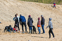 BNPS.co.uk (01202 558833)<br /> Pic: Graham Hunt/BNPS<br /> <br /> Visitors not put off by the coronavirus pandemic flock to the seaside resort of West Bay in Dorset on a day of sunshine and clear blue skies.<br /> <br /> Visitors walking on the beach close together.