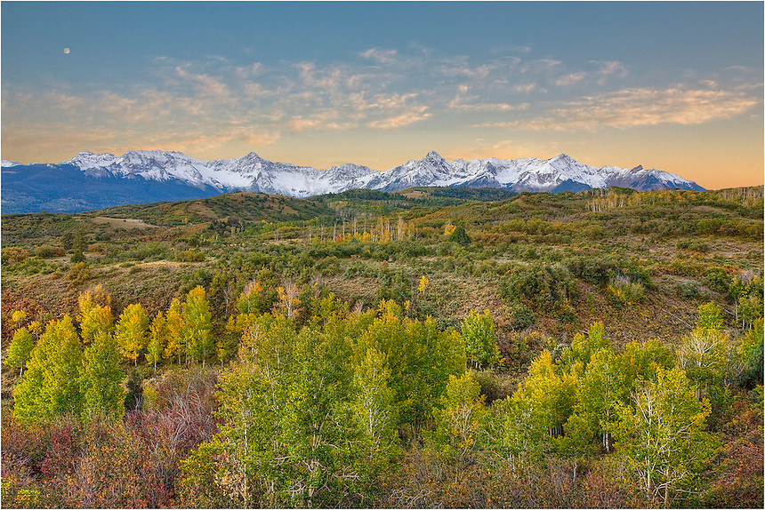 This image from Colorado was taken at the Dallas Divide. The sky was turning orange and the trees, including the aspen leaves, were beginning to change to a nice golden color. This area is a beautiful location in the San Juan Mountain range in Colorado.