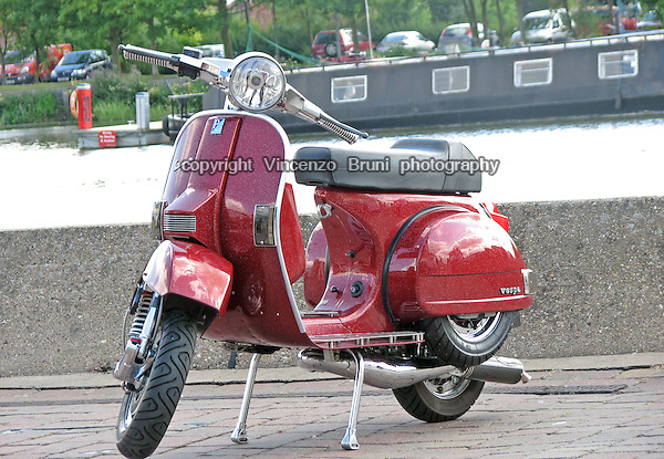A classic Vespa PX with customized paintwork and chroming on show during a rally in England.