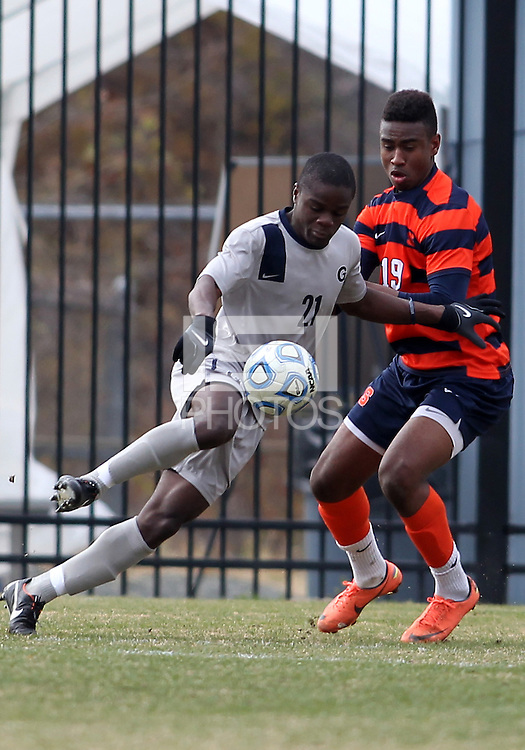 WASHINGTON, DC - NOVEMBER 25, 2012: Melvin Snoh (21) of Georgetown University moves the ball past Tyler Hilliard (19)of Syracuse University during an NCAA championship third round match at North Kehoe field, in Georgetown, Washington DC on November 25. Georgetown won 2-1 after overtime and penalty kicks.