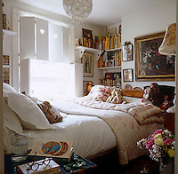 Soft toys sit on quilts at one end of the bed in this feminine English country-style bedroom