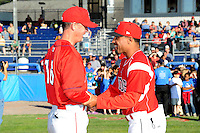Batavia Muckdogs manager Angel Espada #4 greets Gary Cathcart #16 before a game against the Auburn Doubledays on June 18, 2013 at Dwyer Stadium in Batavia, New York.  Batavia defeated Auburn 10-2.  (Mike Janes/Four Seam Images)