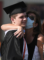 Holli Oliver (right) hugs graduate Griffin Oliver after he received his diploma, Friday, July 17, 2020 during a graduation ceremony at Bentonville High School in Bentonville. Check out nwaonline.com/200718Daily/ for today's photo gallery. <br /> (NWA Democrat-Gazette/Charlie Kaijo)