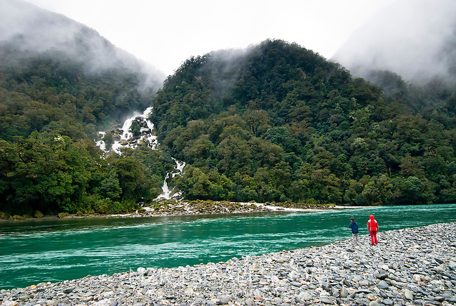 Roaring Billy waterfalls, Haast River and two people - South Westland, West Coast, New Zealand