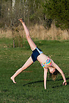 Teenager doing a cartwheel on the grass