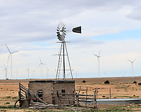 Old windmill with wind generators in the background.