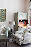 The sitting area of a guest bedroom at the Haymarket Hotel, London. The room is furnished in shades of green with a patterned armchair and painted bureau.