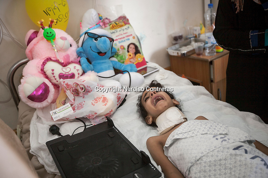 "In this Saturday, Aug. 16, 2014 photo, Maha Shaik Khalil, a 7 yo girl, cries as she lies helplessness on a bed in Al-Shifa hospital in Gaza City. Maha survived after an Israeli bomb targeted her family house in Shuyaja neighborhood during the ""Protective Edge"" military operation in Gaza Strip. Maha is totally paralized from neck down her body due the severe wounds at her spinal nerves. (Photo/Narciso Contreras)"
