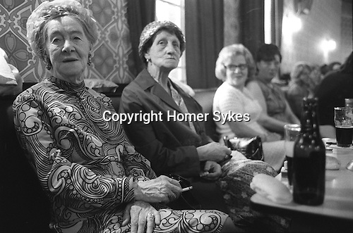 Byker Working Mens Club. Saturday evening, two older senior ladies in their best clothes, patterned dress and hats. Drinking a bottle of Stout and eating a roll. New Castle upon Tyne. 1970s England. ..