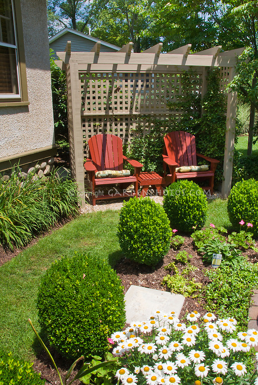 backyard seating and formal garden style landscape with trimmed