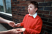 Schoolboy buying drugs in the playground from a drugs dealer. The child is in the process of handing over money for the tablets. This image may only be used to portray the subject in a positive manner..©shoutpictures.com..john@shoutpictures.com